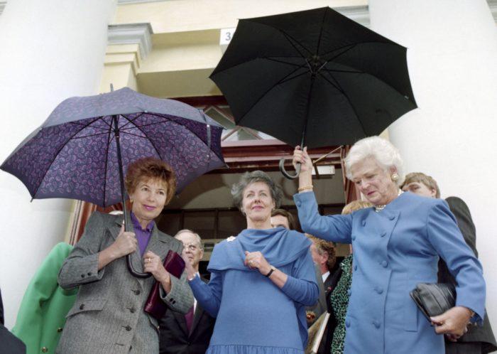 Raisa Gorbacheva, Tellervo Koivisto and Barbara Bush holding umbrellas.