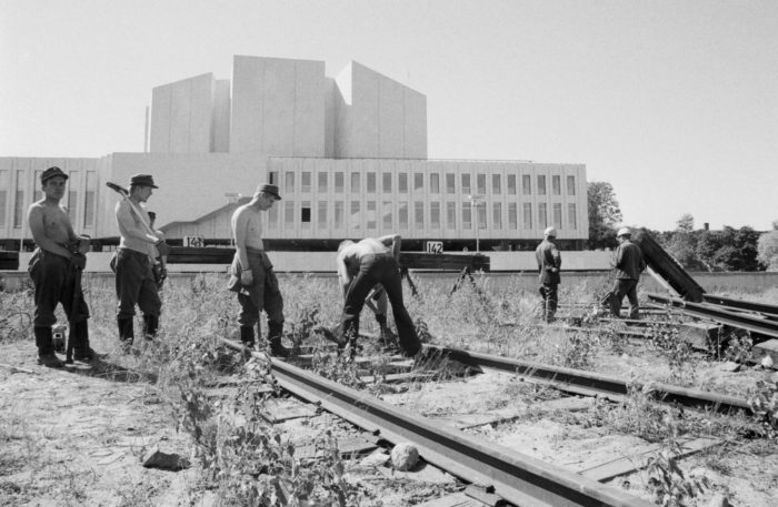 A black-and-white photo of shirtless young men digging the ground next to train tracks, Finlandia Hall in the background.