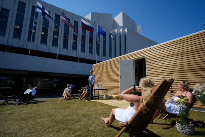 People sitting in the sun outside of a wooden container sauna.