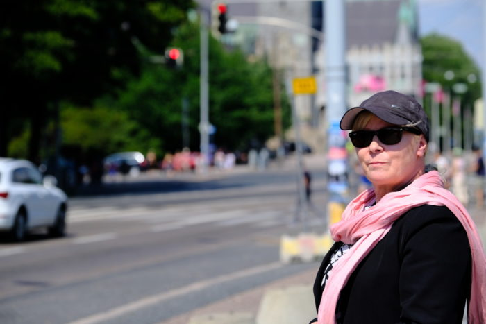 A woman in sunglasses, cap and a pink scarf standing by a road.