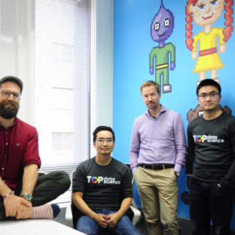 Four men posing in an office with a blue wall decorated with pixel characters.