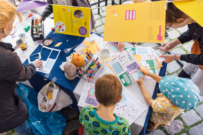 Children gathered around a table filled with stickers, pens, strings and other crafting materials.