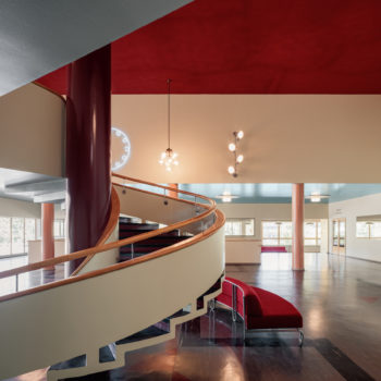 Lasipalatsi lobby; red couches and a white spiral staircase.