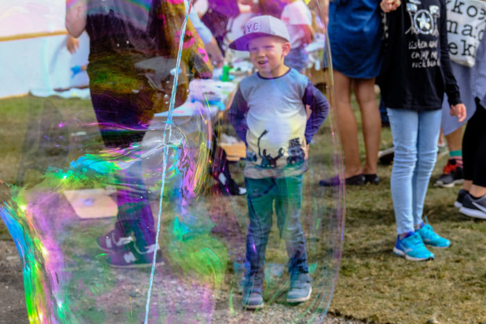 An awed-looking young boy seen through a gigantic soap bubble.