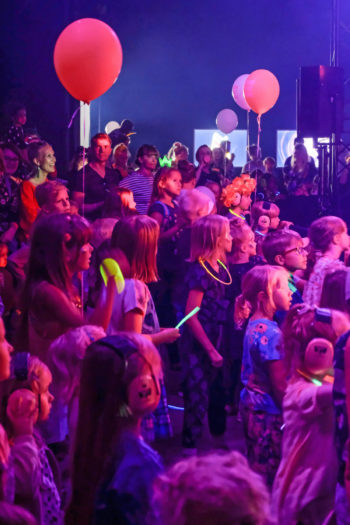 A big crowd of kids in ultraviolet lighting wearing earmuffs and watching something intently.
