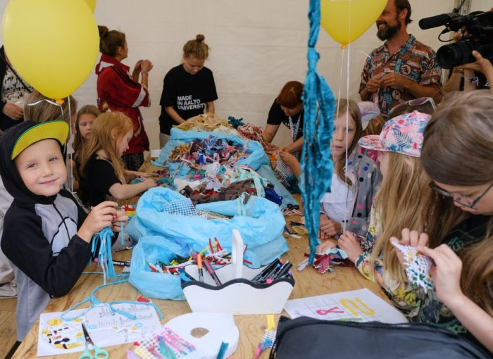 Kids gathered around a table filled with small pieces of textile, pens and other crafting materials.