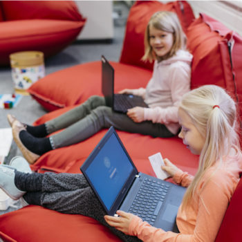Two young girls sitting on a red couch with laptops in their laps.