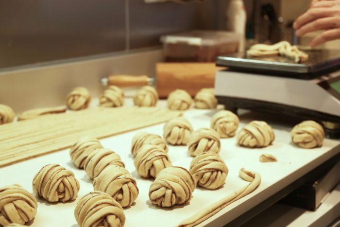 Long and thin strands of cinnamon bun dough rolled into a knot-shaped buns.