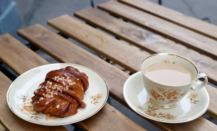 A cinnamon bun on a plate next to a small coffee cup with floral decorations on a wooden table.