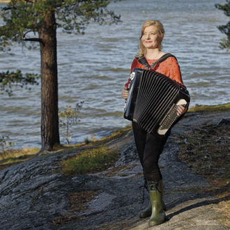 Maria Kalaniemi posing outside by water with her accordion.