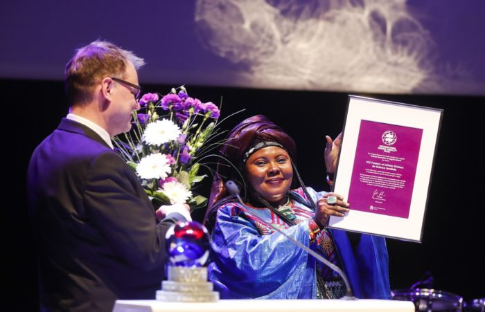 Mariama Moussa holding the International Gender Equality Prize diploma and Juha Sipilä holding a bouquet.