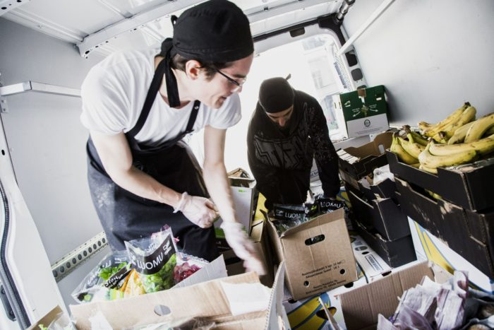 Two people unloading a van filled with different produce, for example vegetables and bananas.