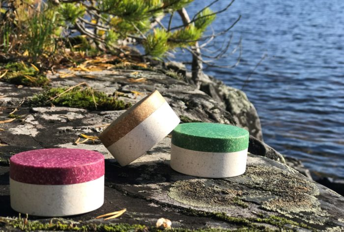 Three small round containers pictures outside on a cliff by water.
