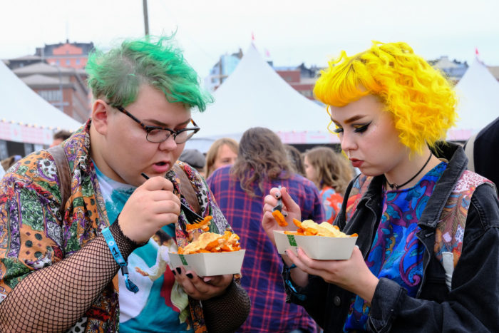 Two girls eating sweet potato fries, white festival tents in the background.