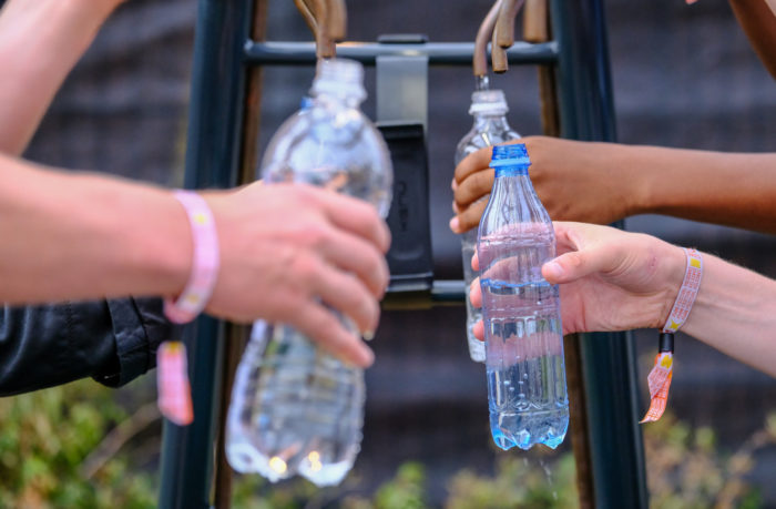 Three pairs of hands filling up water bottles from two taps.
