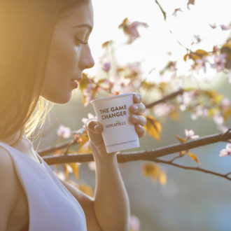 A woman drinking coffee from a disposable cup that says 'the game changer', cherry blossoms in the background.