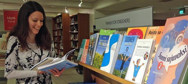 A smiling woman looking at Finnish language books at a bookstore.