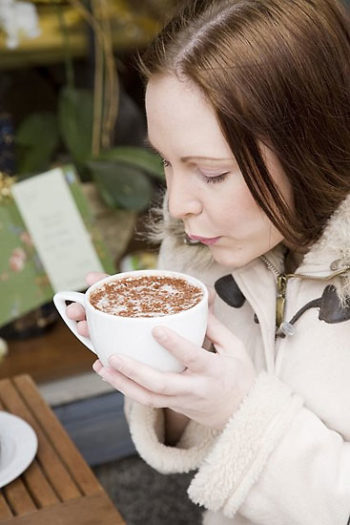 A woman blowing at her cappuccino cup.