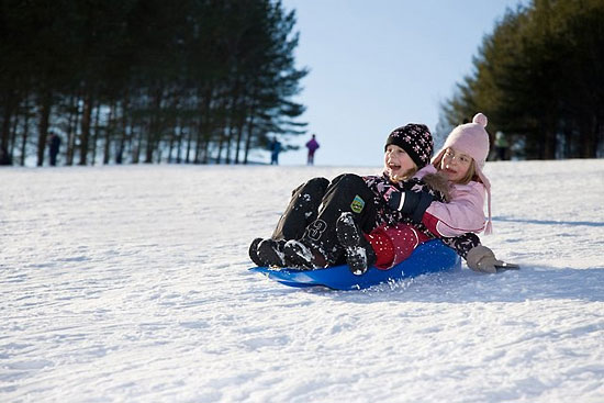 Two smiling children riding their sled.