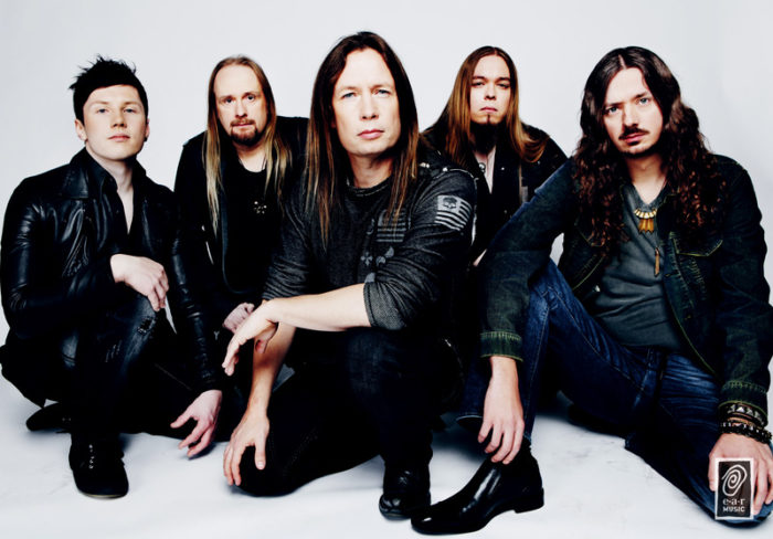 The band Stratovarius pictured sitting down against a white background.