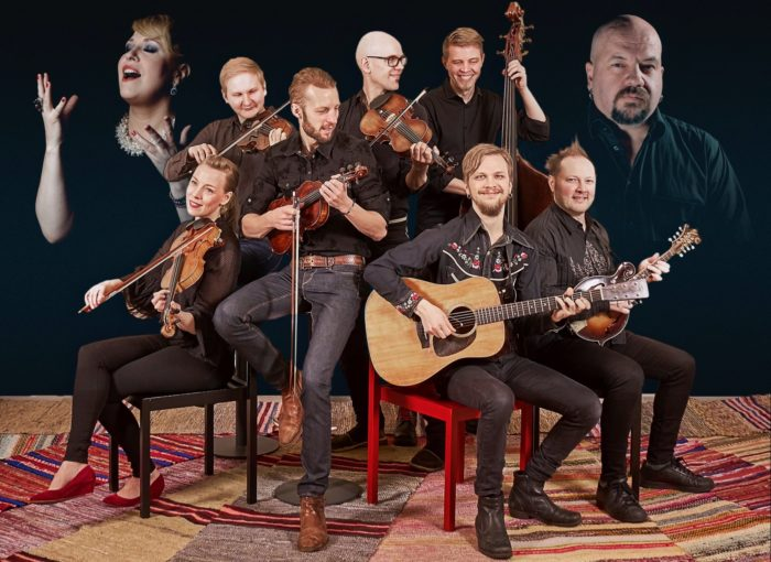 Fiddle band Frigg posing with their instruments, guest singers Johanna Försti and Timo Rautiainen pictured in the bakcground.
