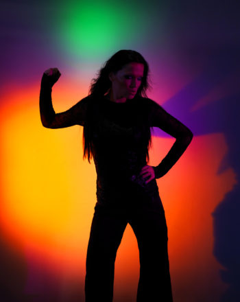 Tarja Turunen dancing with a background of colourful lights.