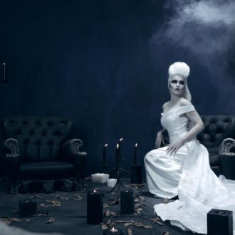 Tarja Turunen in a white dress and wig sitting on a black armchair amidst candles.
