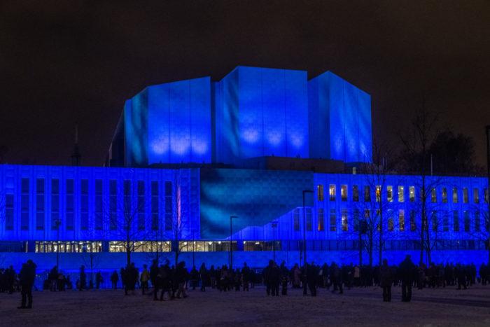 Finlandia hall in darkness, illuminated with deep blue lights.