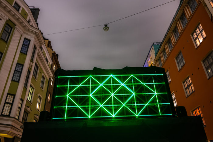 Geometric shapes in green light installed between two buildings.
