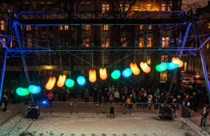 Colourful round lights hanging in a railing, a crowd gathered to watch them.