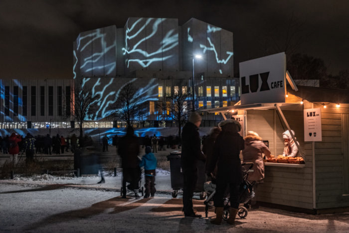 People standing by a small café shed with Finlandia hall in the background.