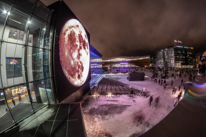 Helsinki Music Centre illuminated with a large full moon.