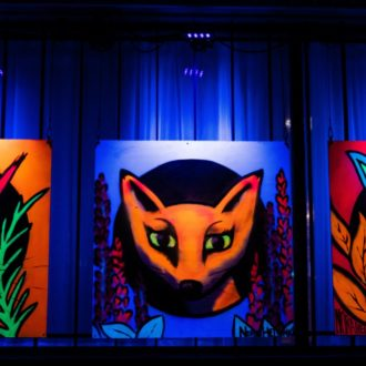 Graffiti showing a squirrel, a fox and a rabbit lit with ultraviolet light.