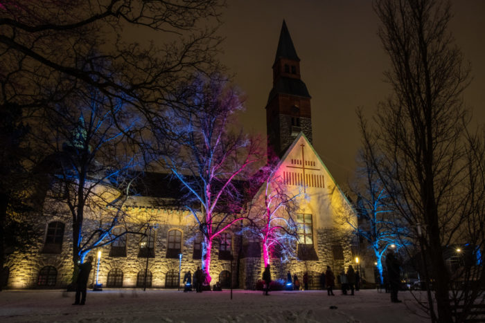 Trees illuminated with pink and blue lights, National Museum in the background.
