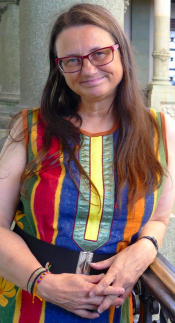 Portrait of a smiling Inger-Mari Aikio dressed in a colourful dress.
