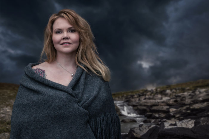 Portrait of author Katja Kettu standing outside in a rocky landscape and a stormy-looking sky.