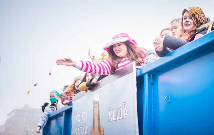 مشاركة المرح: في جميع أنحاء فنلندا، يقوم الطلاب المتنكرون في الموكب برمي الحلوى على الحشود.