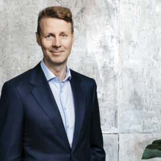 Portrait of Risto Siilasmaa standing in front of a concrete wall and a bookcase.