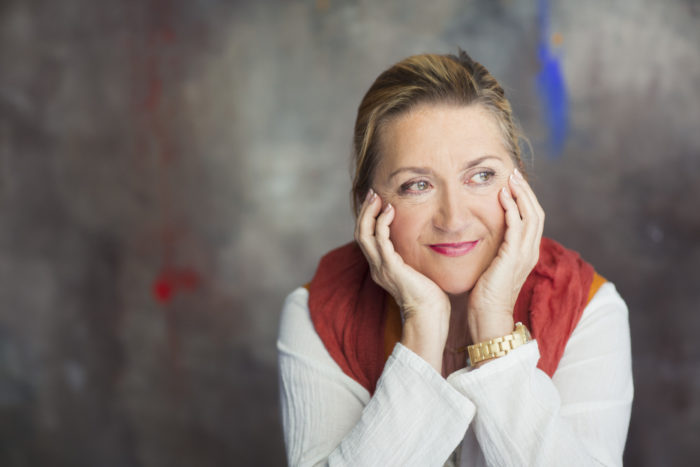 Portrait of author Anja Snellman leaning her face in her hands and looking to right.