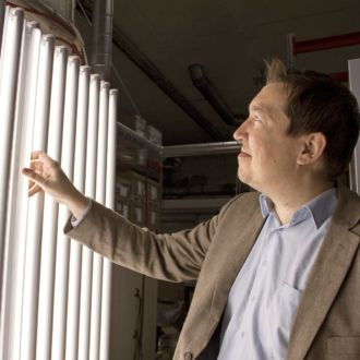 A smiling man looks at a row of LED light tubes.
