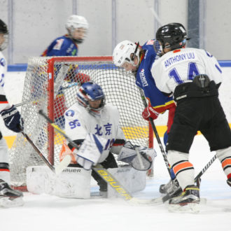 A hockey goalie trying to protect his goal from the opponent's player.