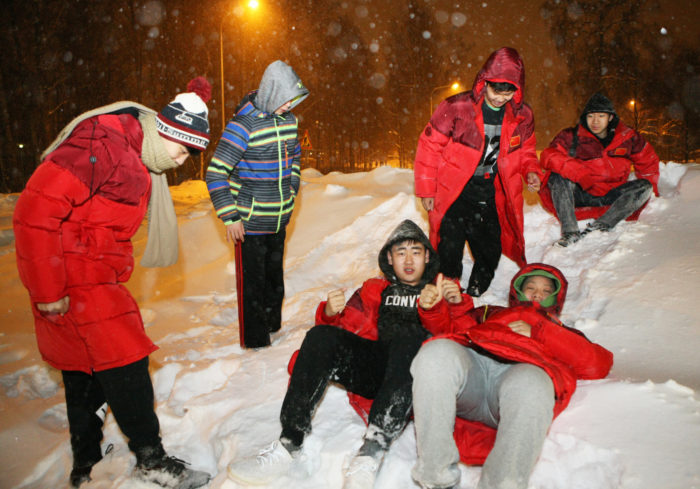 Young Chinese boys lying and playing in a big pile of snow.