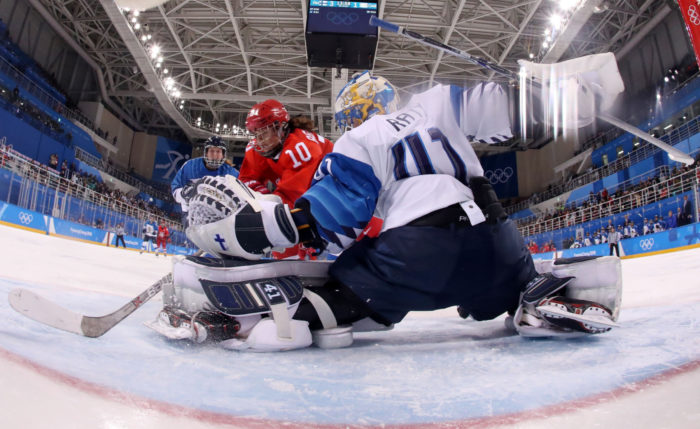 A camera at the back of the net shows Finnish goalie blocking a shot with a glove and a leg out.