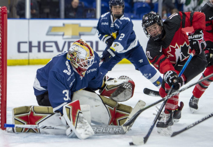 Finland's goalie blocking a shot from a Canadian player.