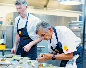 Two focused-looking chefs are plating multiple similar dishes.