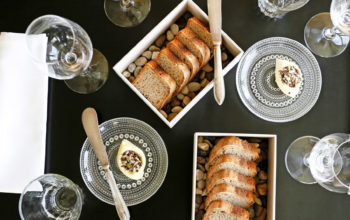 Empty wine glasses and plates of white toast are arranged on a table.
