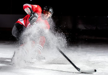 An ice hockey player stops, sending up a cloud of small ice particles.