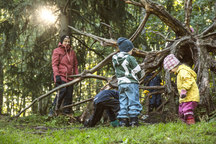 Small children play beside the roots of a fallen tree, with an adult watching nearby.