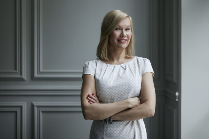 Portrait of a smiling Minna Rytisalo standing in front of a white-paneled wall.