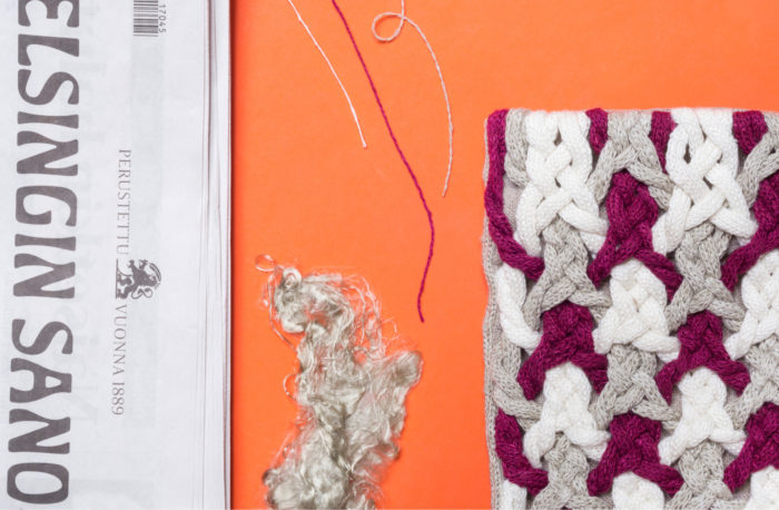 A newspaper, some fibres and fabric made of those fibres on an orange background.